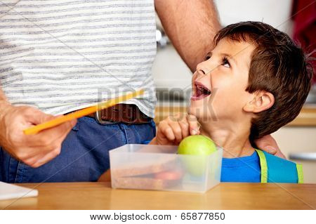happy young boy looking up at dad with healthy apple in lunch box for school