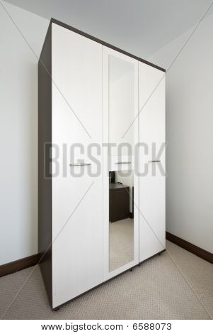 Interior Of Bedroom With A Big White Wardrobe
