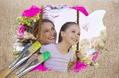 Composite image of mother and daughter in the park against weathered surface with paintbrushes poster