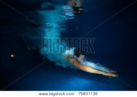 Man with splash swimming under dark blue water