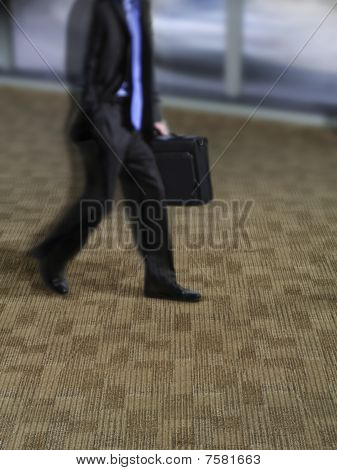 Man on rug with briefcase walking