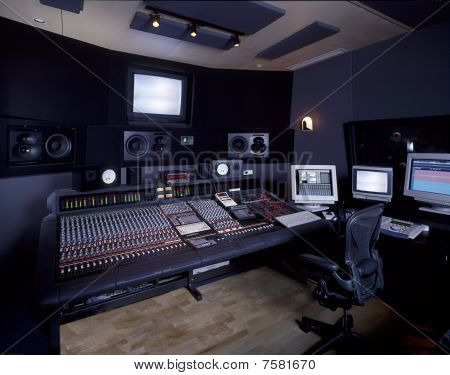 A modern music studio filled with mixing boards, the latest DAW technology and speakers poster