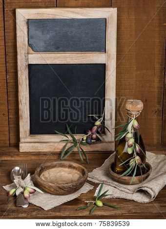 Vintage Table Setting With Olives And  And Antique Blackboard On The Wooden Background