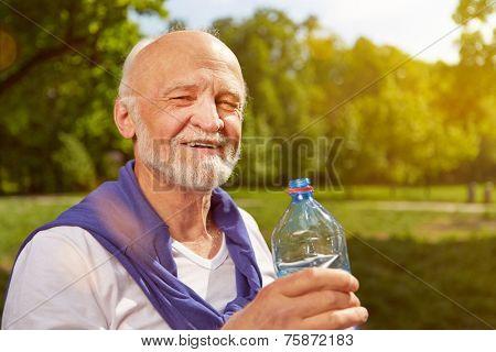 Thirsty senior man drinking fresh water after sports