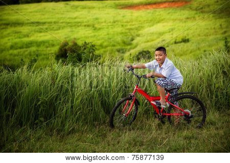 Asian Boy Riding On His Bycicle