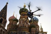 A flying hexacopter without a camera shot from below with the blue skies and blured features of Red Square in the background poster