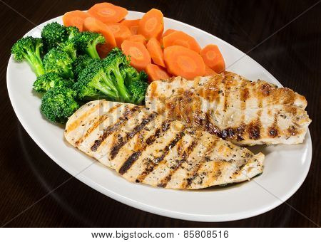 Two pieces of grilled chicken breast, steamed broccoli and steamed carrots arranged on a plate as a dinner entree poster