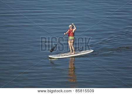 Woman stand up paddleboarding on open water