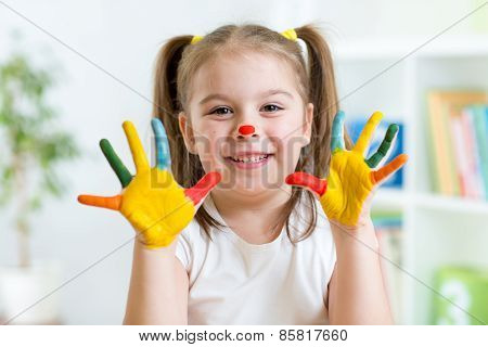 Five year old girl with hands painted in colorful paints