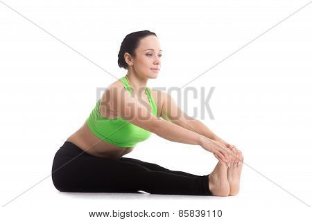 Serene fitness girl does yoga training seated Forward Bend pose (Intense Dorsal Stretch) Paschimottanasana stretching back shoulders hamstrings poster