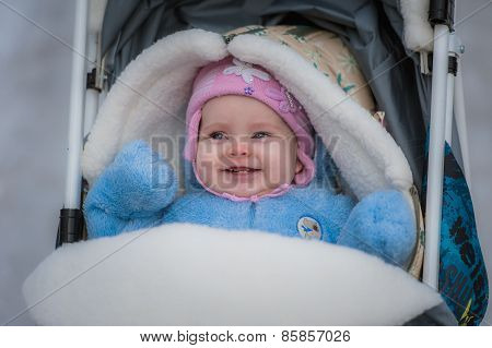 Smiling baby sitting in sledge. Happy infant girl
