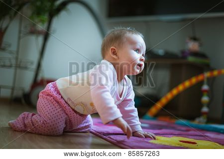 Adorable baby girl crawls on all fours floor at home. Smiling