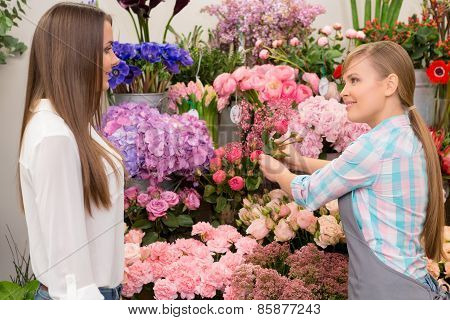 Florist displaying floral arrangements to the customer