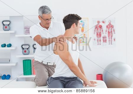 Doctor doing back adjustment in medical office poster