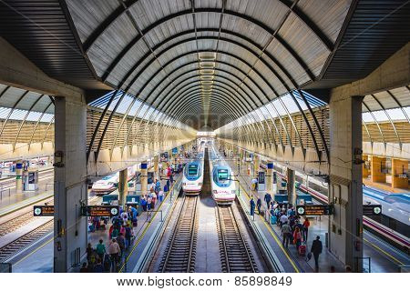 SEVILLE, SPAIN - OCTOBER 8, 2014: Passengers and trains at Santa Justa Station. The station is the third busiest in Spain with an estimated 8 million passengers annually.