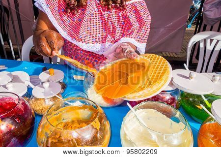 Closeup black lady wearing colorful dress with street food store preparing a traditional Colombian o
