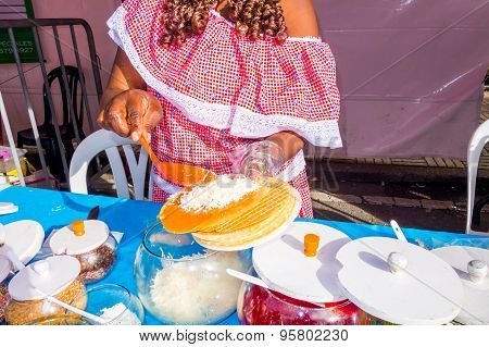 Closeup black lady wearing colorful dress in street food store preparing a traditional Colombian obl