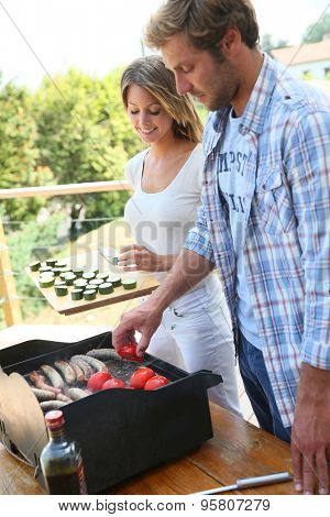 Couple preparing bar-b-q meat and vegetables
