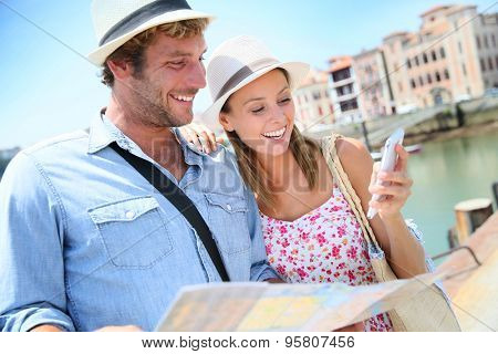 Couple of tourists at seaside resort looking at city map poster