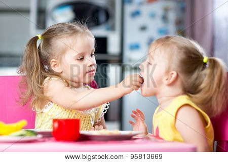 Little Children Toddlers Eating Meal Together, One Girl Feeding Sister In Sunny Kitchen At Home