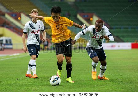 May 27, 2015 - Shah Alam, Malaysia: Malaysia's Joseph Kalang (17) takes on two Tottenham Hotspur defenders (white jersey) in a friendly match. Tottenham Hotspur is on a Asia-Australia tour.