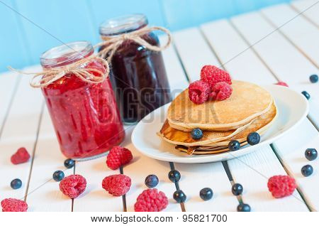 Stack of wheat golden pancakes or pancake cake with freshly picked raspberries on a dessert plate, g