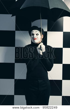 Male mime artist stands under an umbrella in the rain and smiles. Chess board background.