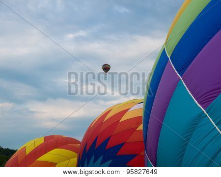 patterns of three hot air balloons getting inflated for lift off