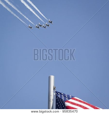 NEW YORK - MAY 22 2015: US Air Force Thunderbird F-16 jets fly in a diamond formation over an American Flag with precision during Fleet Week NY 2015 as part of Memorial Day celebrations in Manhattan.