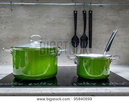 Two green enamel stewpots on black induction cooker poster