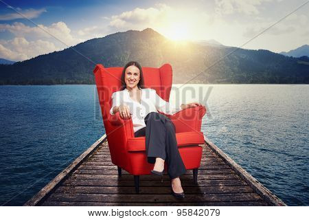 smiley woman resting on the red chair on moorage with beautiful landscape