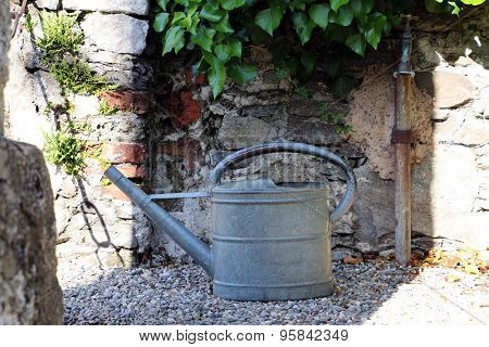 Metal watering can on gravel in front of the wall