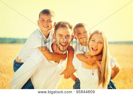 Happy Young Family with two children walking on wheat summer field. Healthy mother, father and little sons enjoying nature together, outdoors. Healthy Smiling Dad, Mom and kids together. Harvest