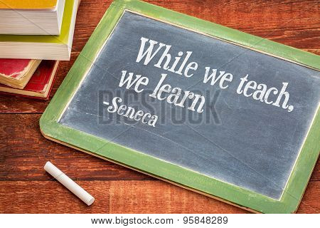 When we teach, we learn - a quote from Seneca on a  blackboard with a white chalk and a stack of books against rustic wooden table