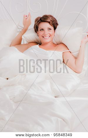 Smiling woman laying in bed