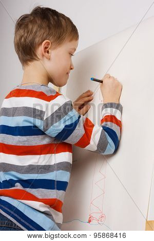 Little boy drawing with pencil on easel