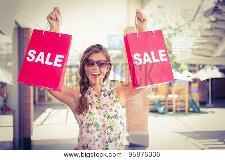 Portrait of euphoric woman holding two sale shopping bags at the shopping mall