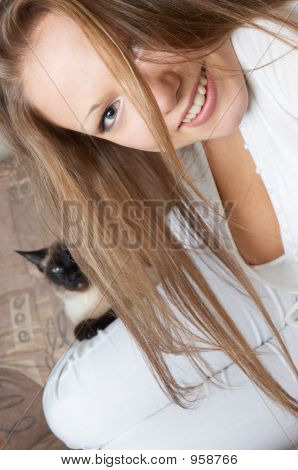 young smiling girl in white with cat sitting on her leg poster