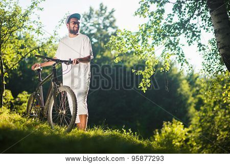 Smiling Sport Boy Stand On A Grass With Bicycle Outdoor
