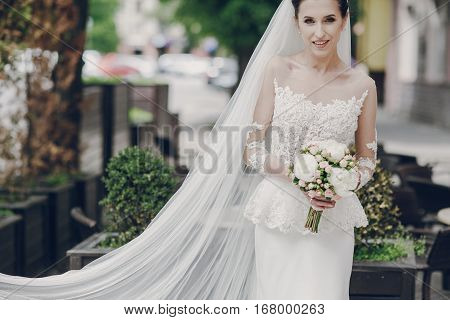 bride standing at a table with a bouquet of flowers