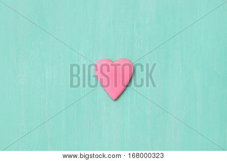 Top view on a little gingerbread cookie in shape of heart on light blue background. Flay layout. Love Valentines's day concept