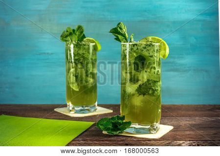 A photo of mojito cocktails with mint leaves and wedges of lime, on a vibrant teal wooden background with copy space. Selective focus