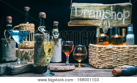 Counter in dram shop. Old wine bottles and glasses full of drinks. Wood sign in beam of light. Concept for sign of online or offline dram store