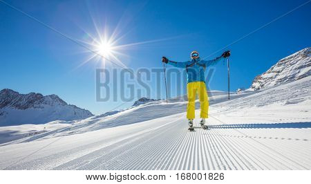 Skier on piste in sunny day with hands up. Skiing concept. Alpine ski resort in Zugspitze, Germany.