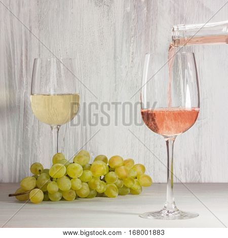 Rose wine poured into a glass, with white wine in the background, with a bunch of grapes, on a wooden texture with copy space