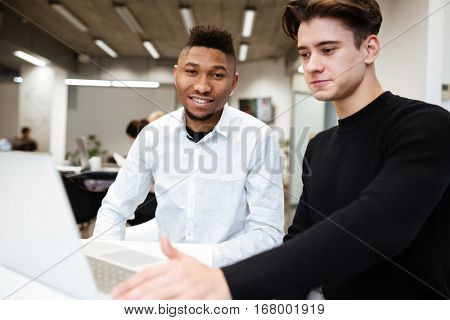 Photo of two students sitting in library and using laptop computer. African guy looking at camera. Caucasian man look at laptop.