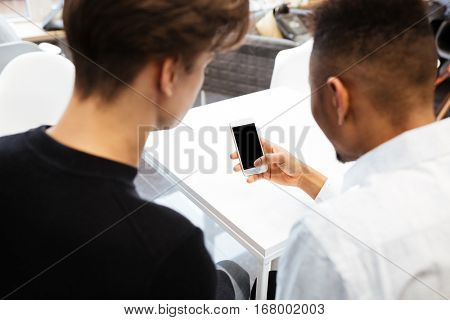 Back view image of two young students sitting in library and using cellphone. Looking at cellphone display.