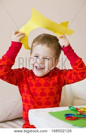 Portrait of cute smiling kid boy making crafts of colour paper and having fun. Child cutting paper. Lifestyle and education concept