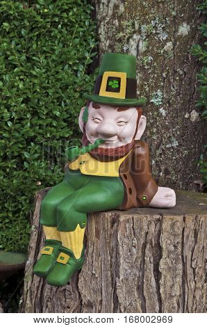 Leprechaun smiling and sitting on a tree trunk with pipe, green and gold suit and hat