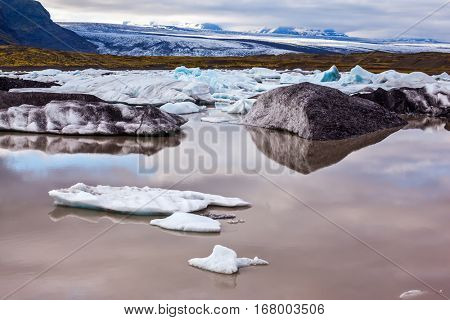 The picturesque lake with splinters of ice floes formed by thawed snow of grand glacier Vatnajokull.  Summer in Iceland. The concept of extreme northern tourism